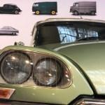 Voorzijde van een metaalgroene Citroën ID 20 Familiale uit 1974, waarbij vooral de massieve koplamp de hoofdrol opeist. In de achtergrond is een poster te zien met diverse andere Citroën oldtimers.