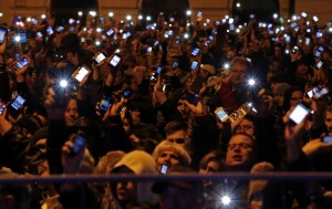 Hungarians hold up cell phones in protest of Internet tax 2014 Photo: PBS TWIMG