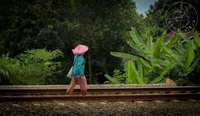 Señora en el campo caminando por lor riéles del tren.