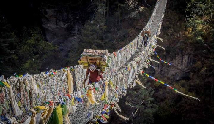 Porteadores cruzando un puente colgante