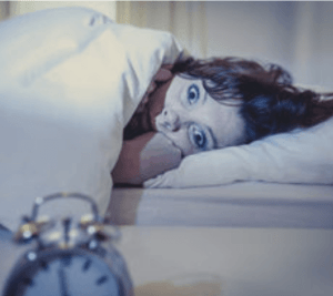 Stock photo image of a woman lying in bed, distressed.
