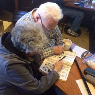 """A stranger took this photo of my parents doing their daily crossword together in a cafe. My mother writes, """"This is not an unusual event.... One lady even paid for father's drink before I got to the cashier because she saw us walk into the store arm and arm."""""""