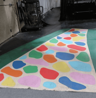 Picture of colorful painted stones on a curving walkway, on the floor of a TV studio.