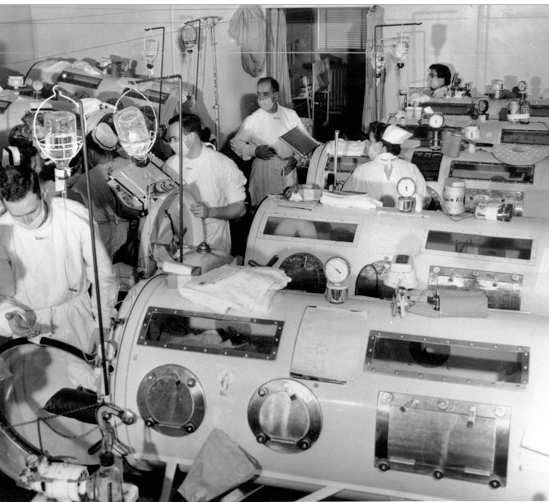 """Rows of """"iron long"""" respirators being tended to by a small army of masked doctors and nurses."""