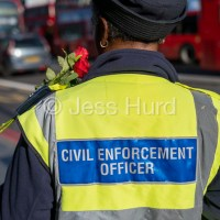 Civil Enforcement Officer, traffic warden, with the flowers she received on Valentine's Day. Brixton, Lambeth, South London.