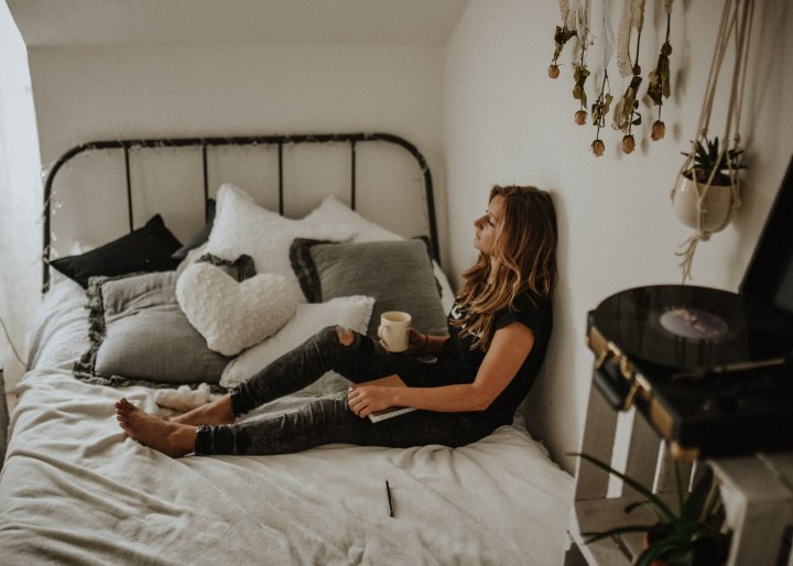 sad girl sitting on bed with coffee