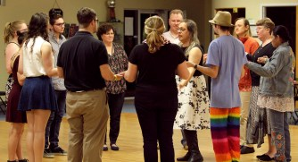 Dancers of all ages gather around to listen to dance teacher, Stephanie Marie give instructions about the basics of contra dance.