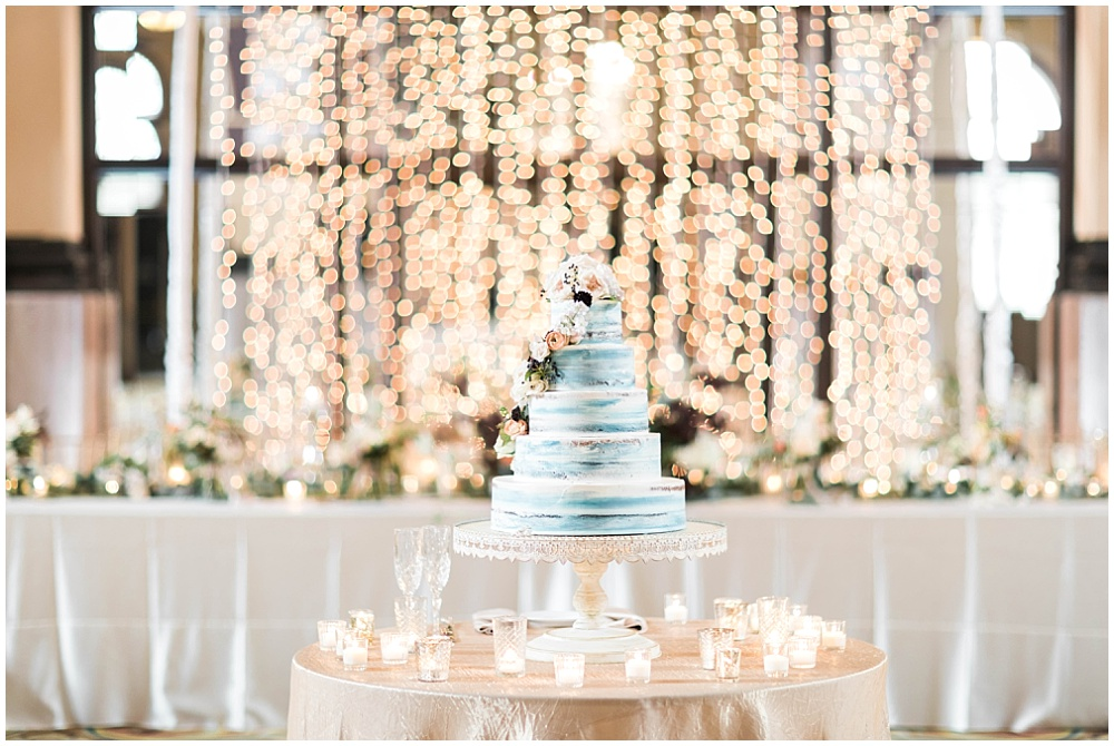 blue naked cake; white bistro twinkle lights; white antique pedestal cake stand; Mexican inspired gold & floral wedding; Crowne Plaza Indianapolis Downtown Union Station; neutral floral and greenery wedding|Cory + Jackie and Jessica Dum Wedding Coordination