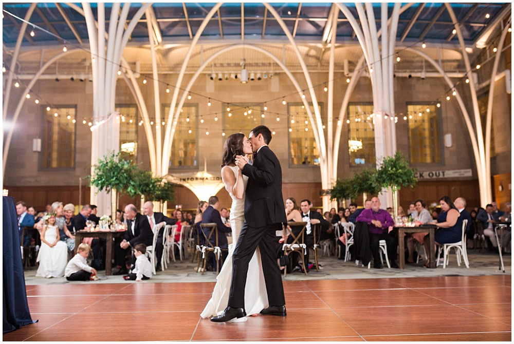 Bride and groom first dance under draped bistro lighting strung above. | Coral and navy Cape Cod-inspired downtown Indianapolis library wedding with Gaby Cheikh Photography and Jessica Dum Wedding Coordination