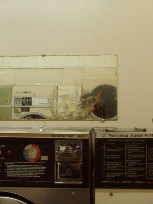 self portrait in gritty mirror at the laundromat