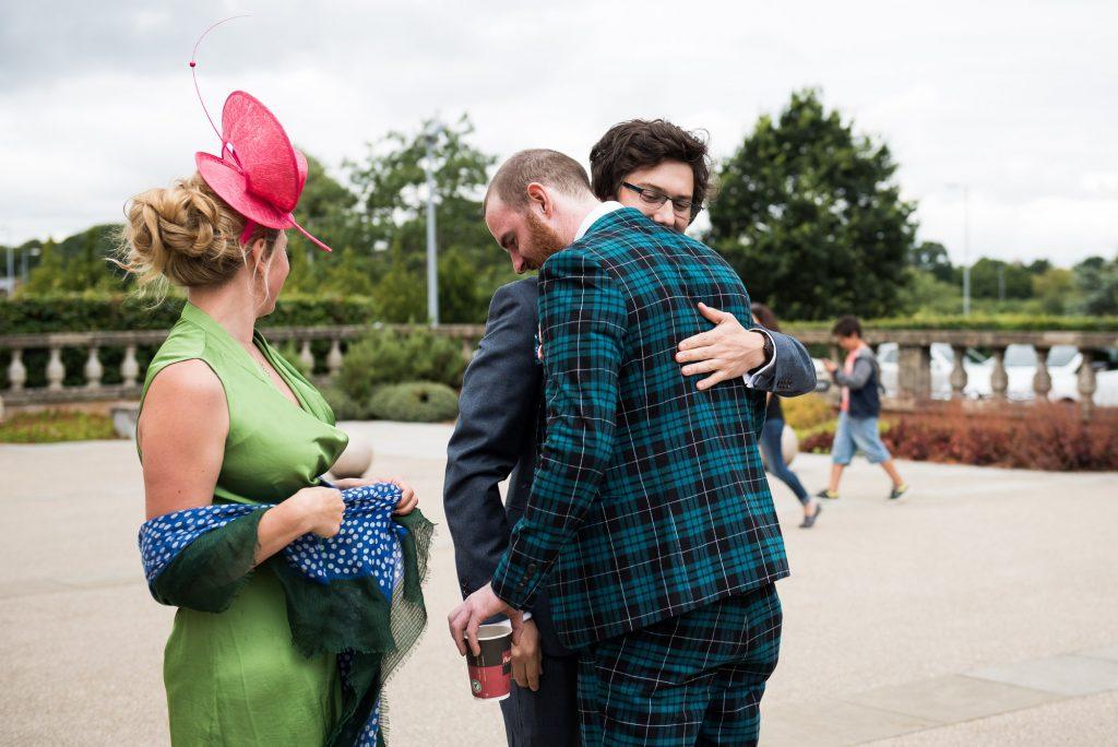 Quirky Groom wearing tartan suit hugs wedding guest Berkshire theatre wedding