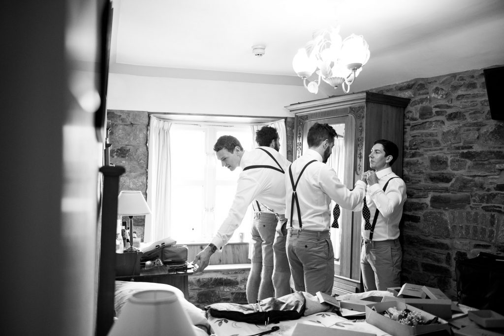 Groom with groomsmen preparing pre wedding photography Cornwall