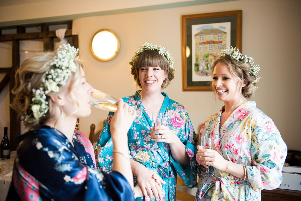 Bride with bridesmaids drink champagne wearing floral robes and floral crowns Driftwood Spars Wedding