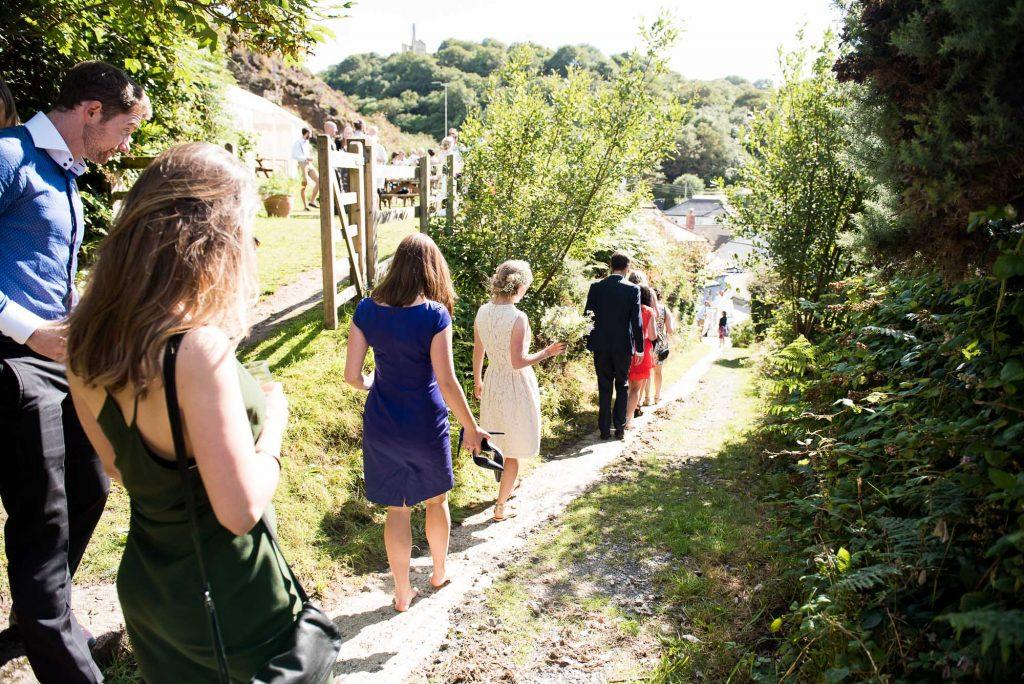 Wedding guests walking sunny rustic beach wedding Cornwall