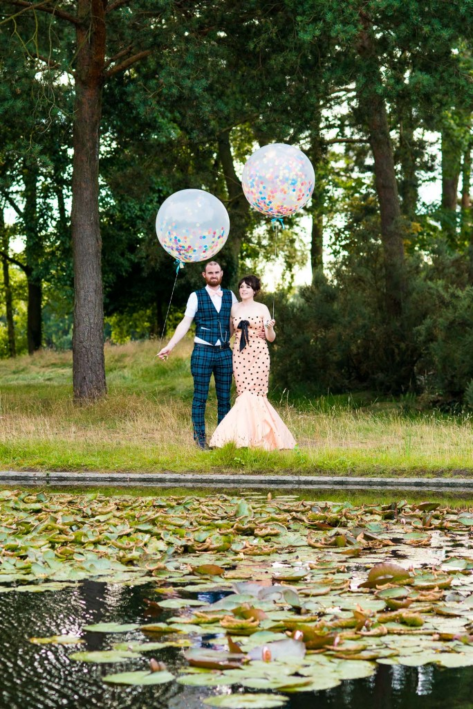 Punk inspired wedding - Creative wedding portrait alternative dressed bride with groom holding colourful balloons Berkshire