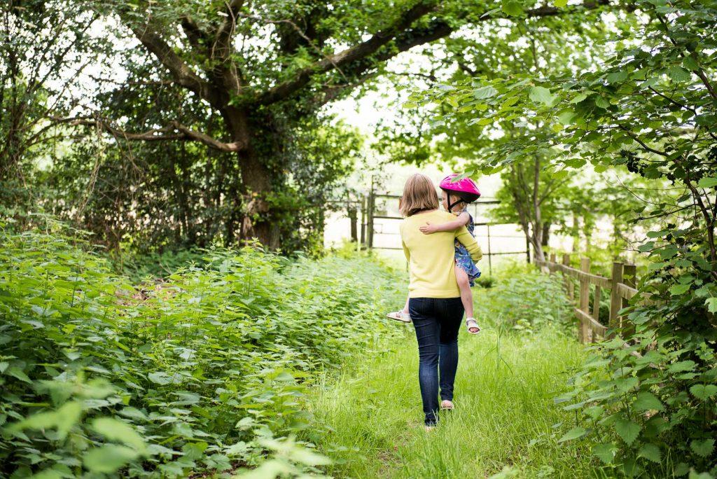 Mum carries daughter garden walk