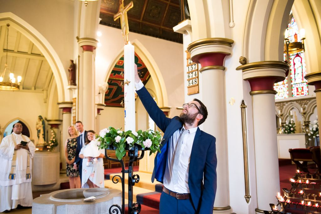 Godfather lights a candle in Christening ceremony Chelmsford