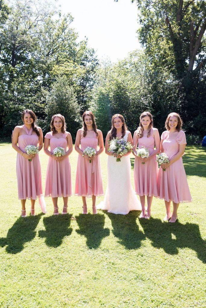 Bride with pastel pink bridesmaids Surrey Barn Wedding