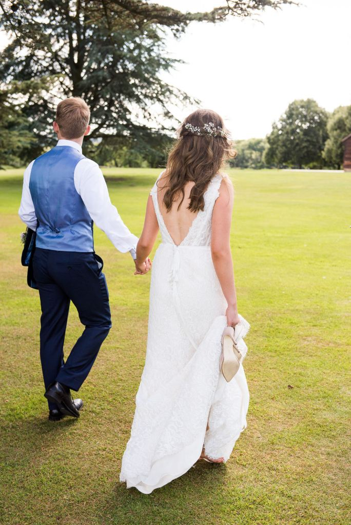 Natural wedding portrait Surrey Loseley Park wedding. Bride wears a gorgeous Miss Bush Bridal dress and groom in navy suit.