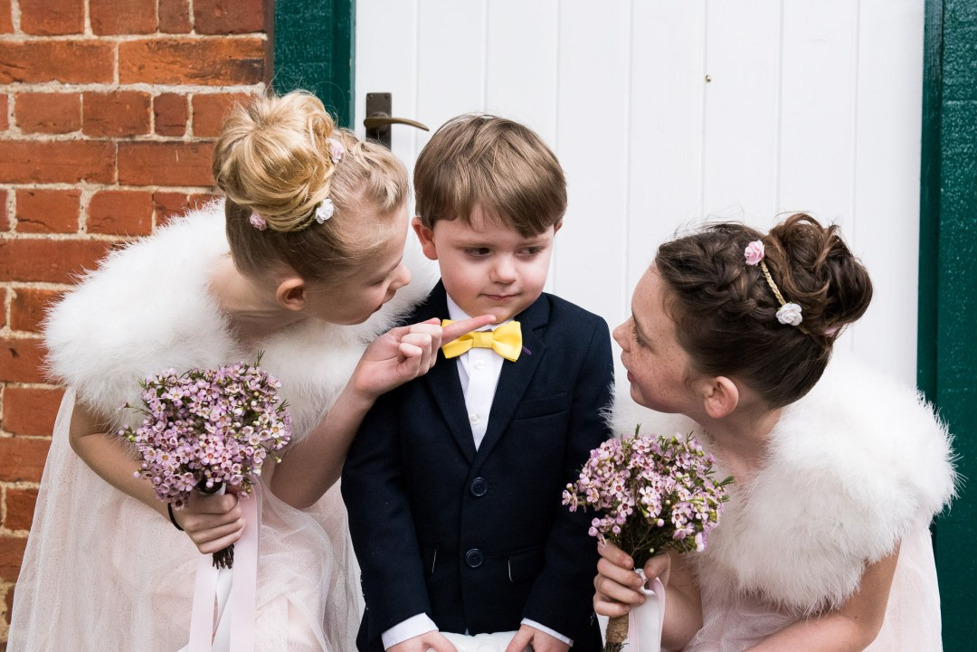 Flower girls trying to convince the ring bearer to smile