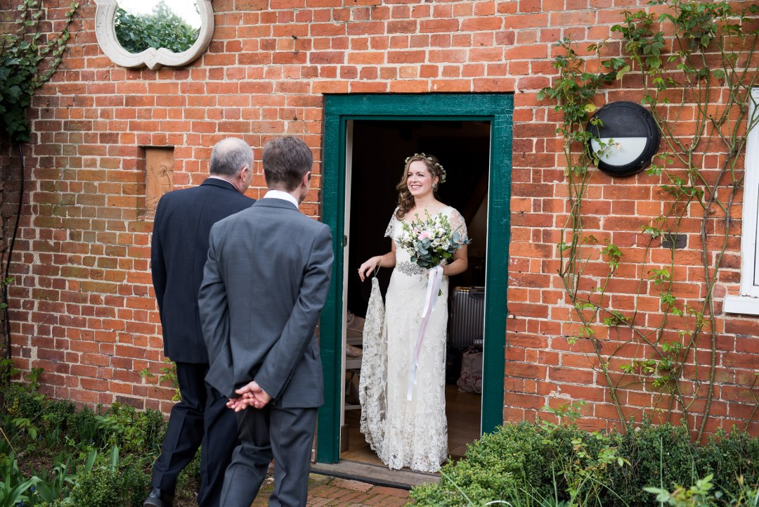 bride greeted by both her dads to walk her down the aisle