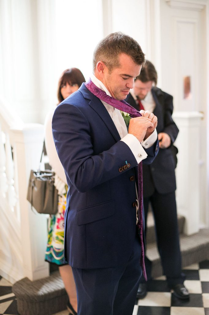 Groom putting finishing touches to his suit Surrey wedding