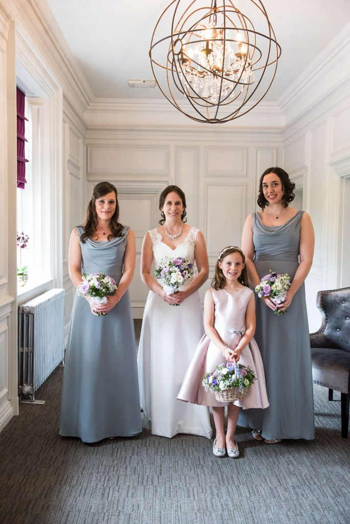 Elegant bride and bridesmaids in pastel blue dresses Surrey wedding