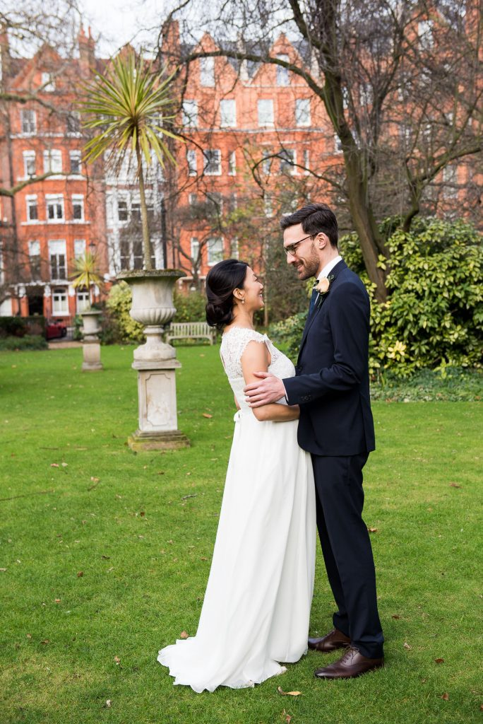 Lace bride with groom wearing navy blue suit London wedding portrait
