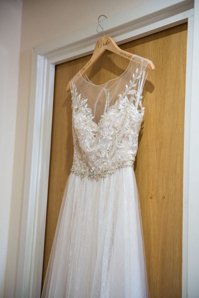 Ashridge House Wedding. Natural Wedding Photography. Bridal preparation Berkhamstead Brides dress hanging in doorway.