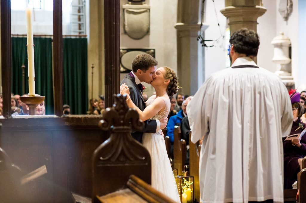 Ashridge House Wedding. Natural Wedding Photography. Couple share their first kiss in family church.