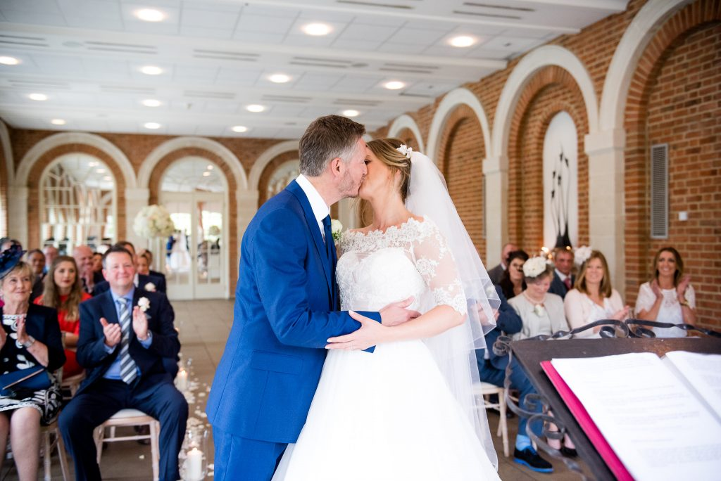 Great Fosters. Natural Wedding Photography. The Newly Married Couple Share Their First Kiss.