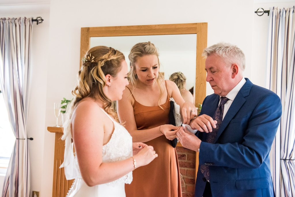 Outdoor Wedding Ceremony, Surrey Wedding Photography, Bride and Her Sister Help Their Dad With His Cufflinks