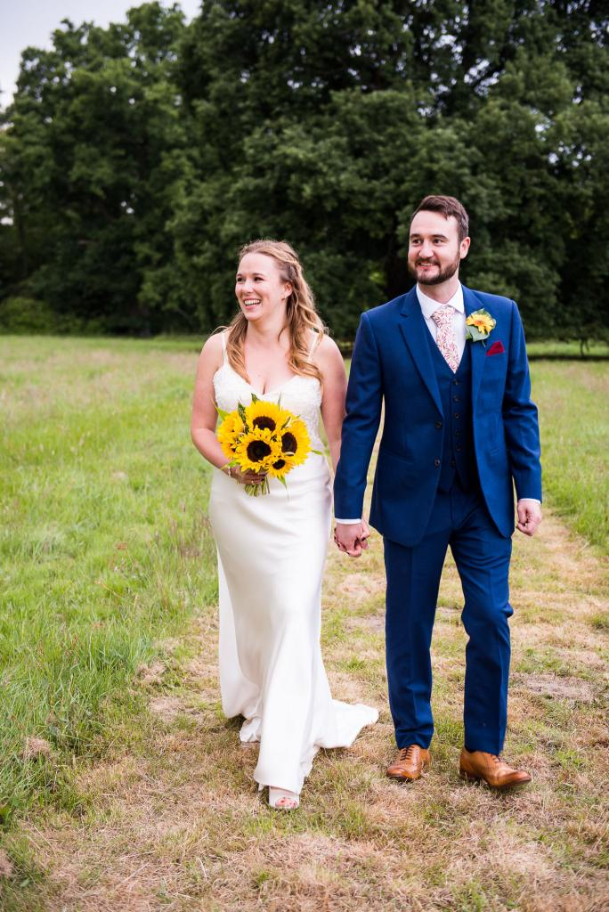 Bride and Groom Walk Together In A Field