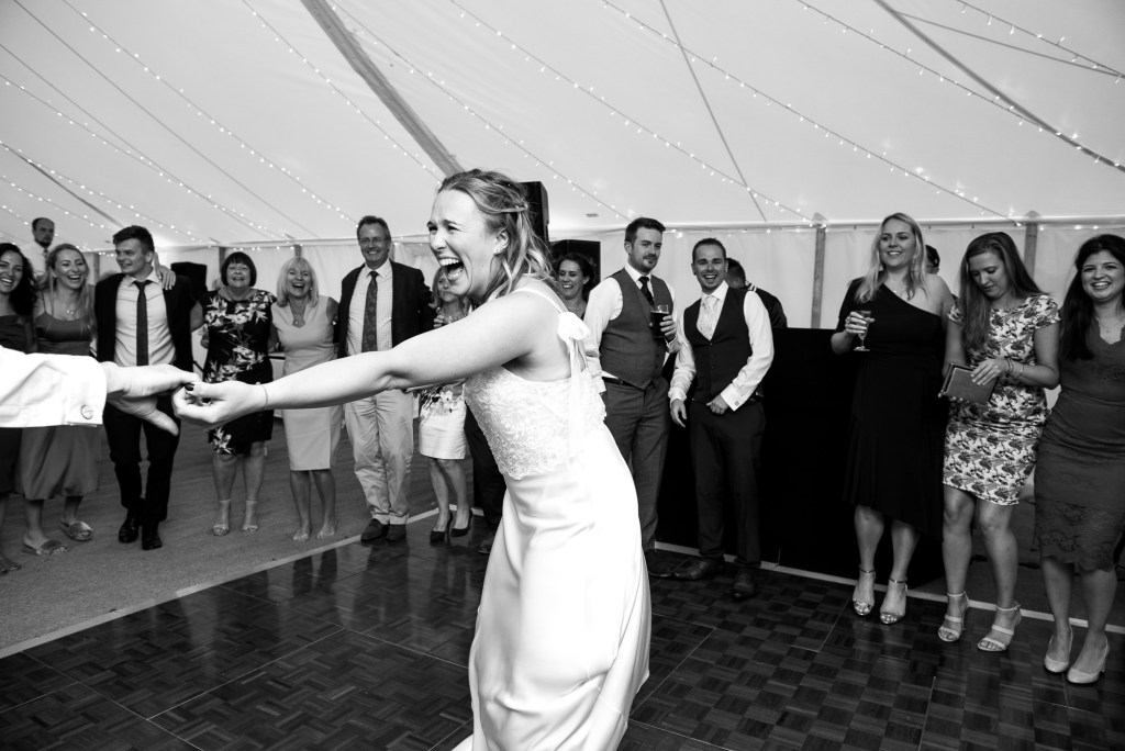 Black and White Photograph Of Bride and Groom Share an Energetic and Lively First Dance