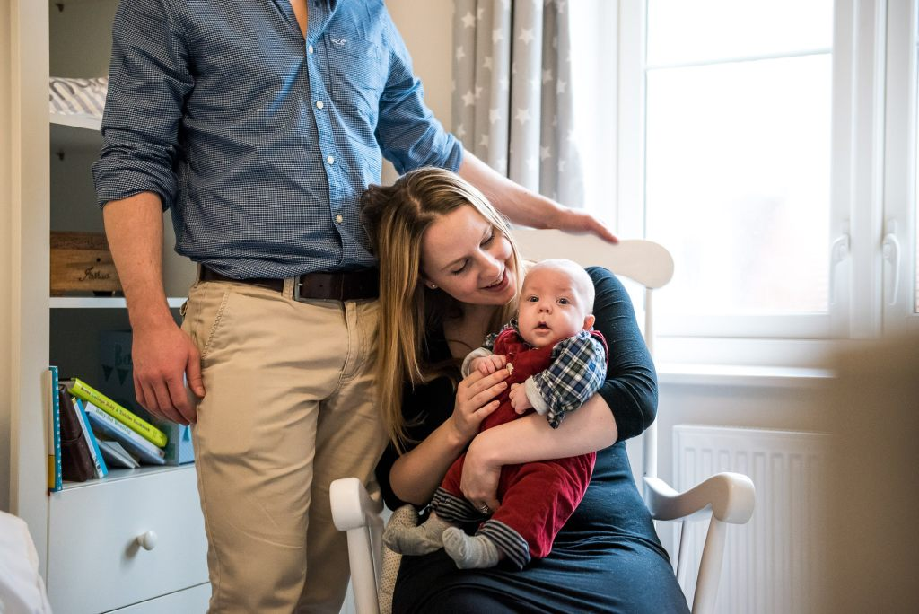 Newborn Photography Guildford, Candid Photograph of Mother, Father and Baby in Nursery