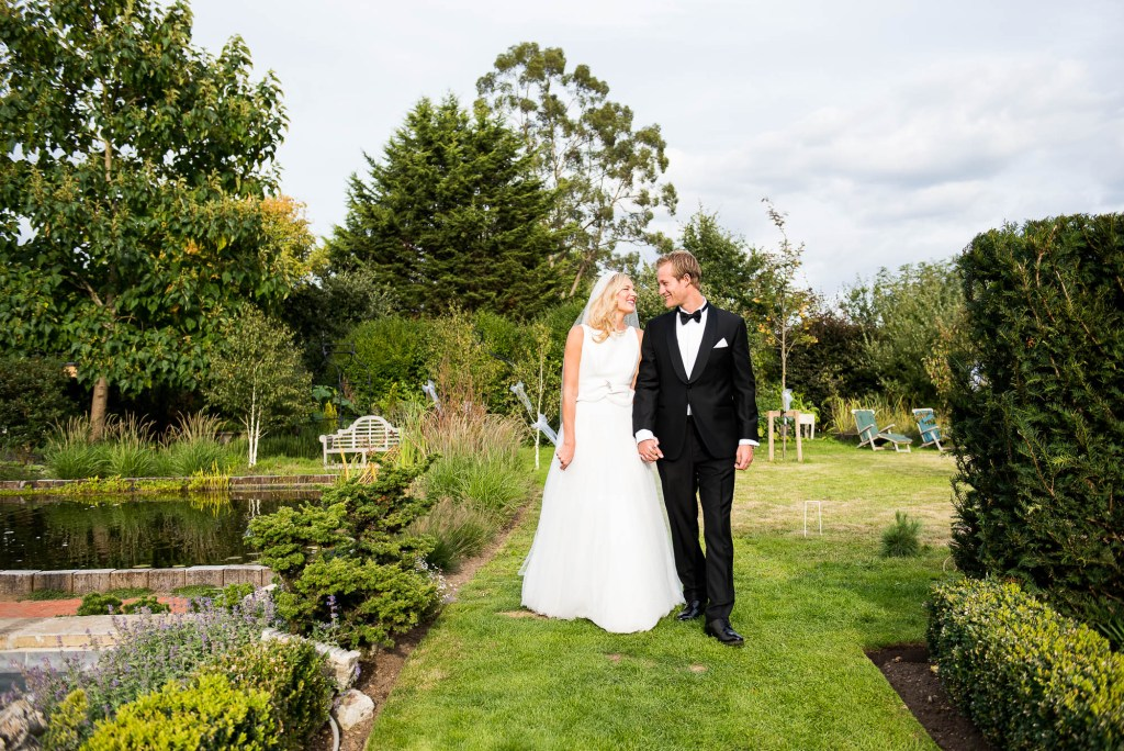 Outdoor Wedding Photography Surrey, Stylish Couple Walking Naturally Hand In Hand Smiling Naturally At Each Other