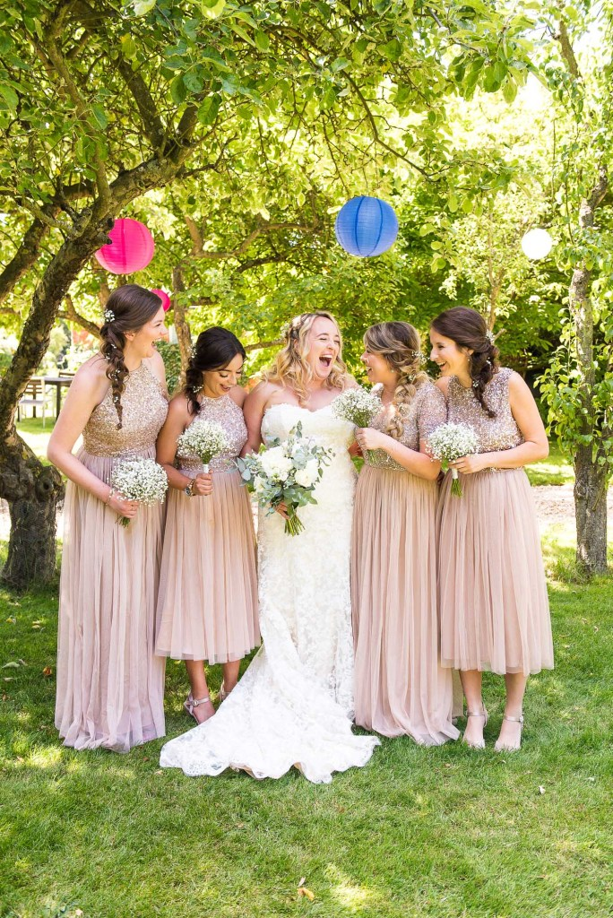 lgbt wedding photographer, beautiful bride laughs naturally with her bridesmaids under coloured lanterns
