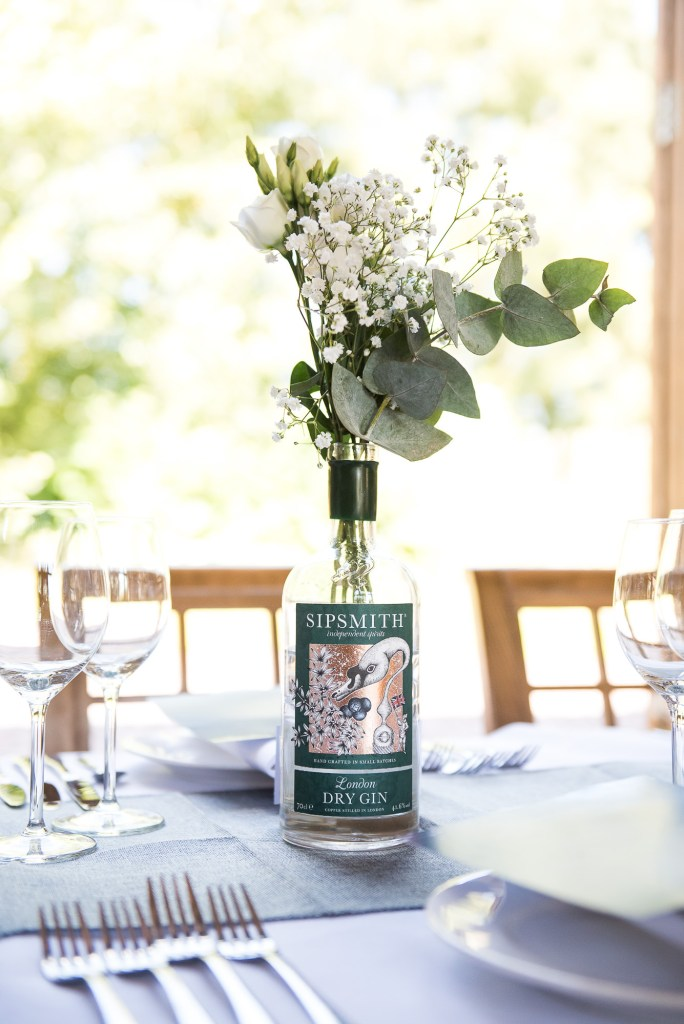 lgbt wedding photographer, wedding breakfast table decorated with vintage gin bottles and botanical florals