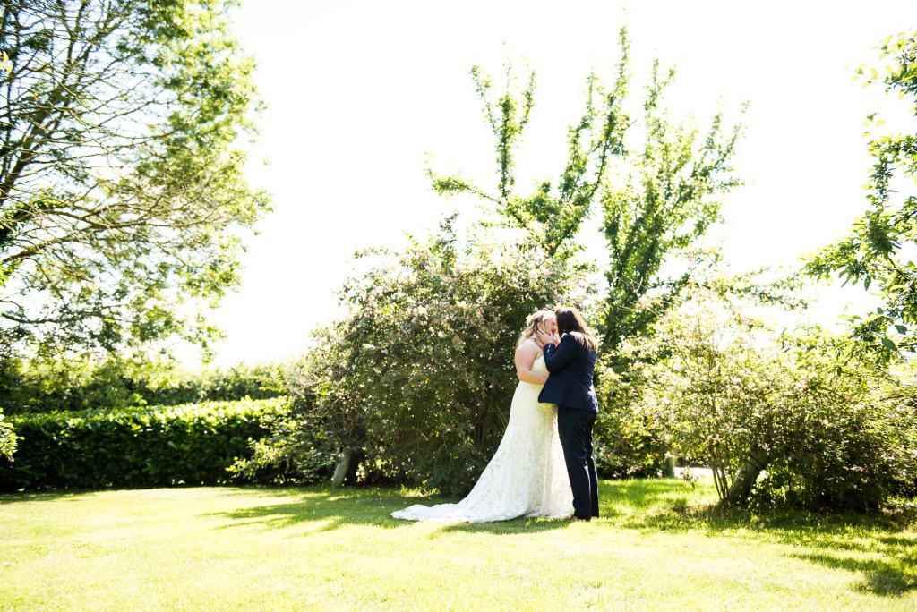lgbt wedding photographer,  same sex couple embrace in the sunshine