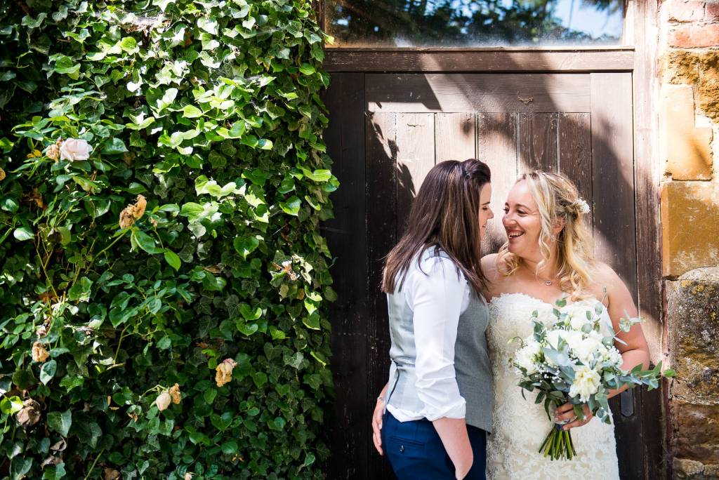 lgbt wedding photographer, Brides look lovingly into each others eyes in a close embrace, Dodmoor House Wedding