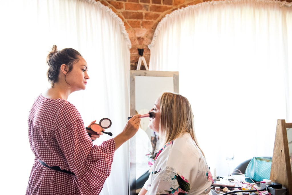 lgbt wedding photographer, Bride having make up put on by make up artist in lovely light room
