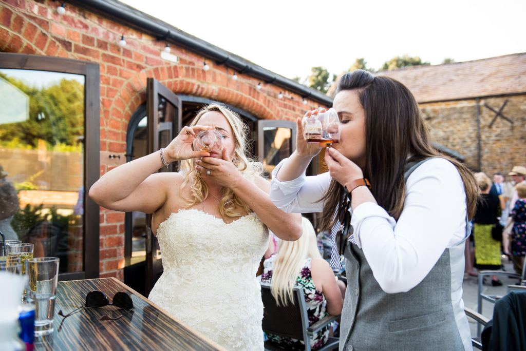 lgbt wedding photographer, two brides do shots together at the wedding bar