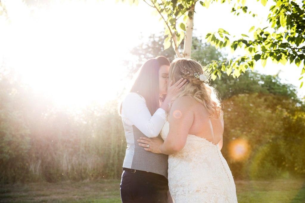 lgbt wedding photographer, brides share a kiss together at sunset