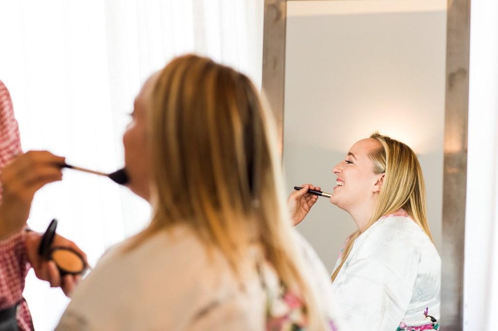 lgbt wedding photographer, Bride having make up put on by make up artist in lovely light room