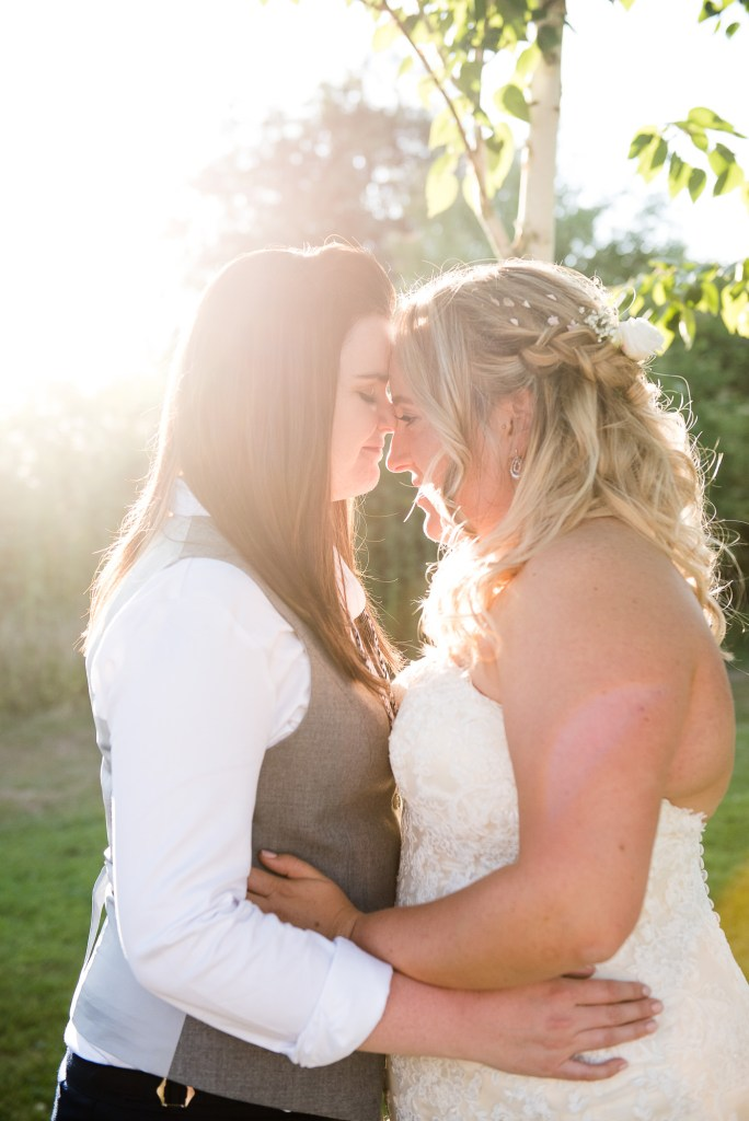lgbt wedding photographer, same sex couple embrace each other at golden hour