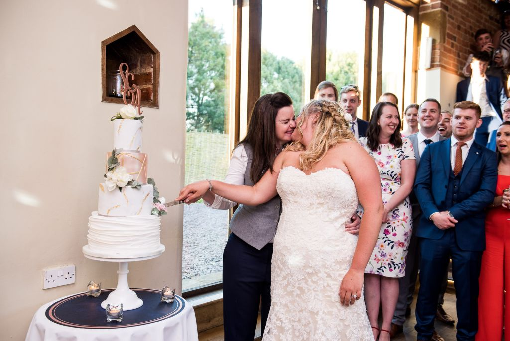 lgbt wedding photographer, same sex couple share a kiss as they cut the cake