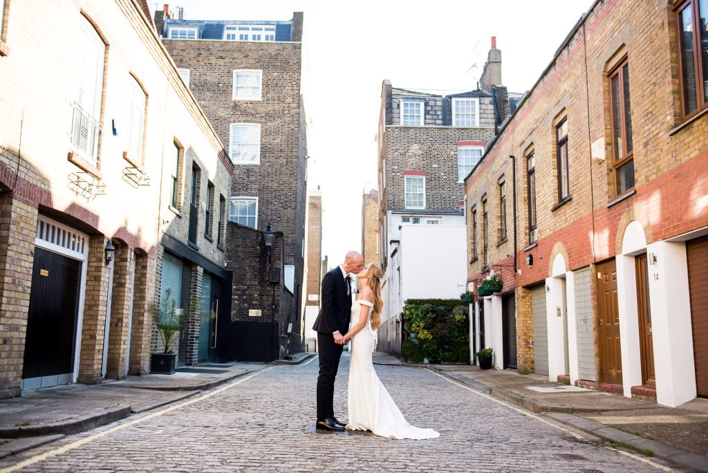 Old Marylebone Town Hall Wedding, bride and groom share a kiss in traditional London Mews street