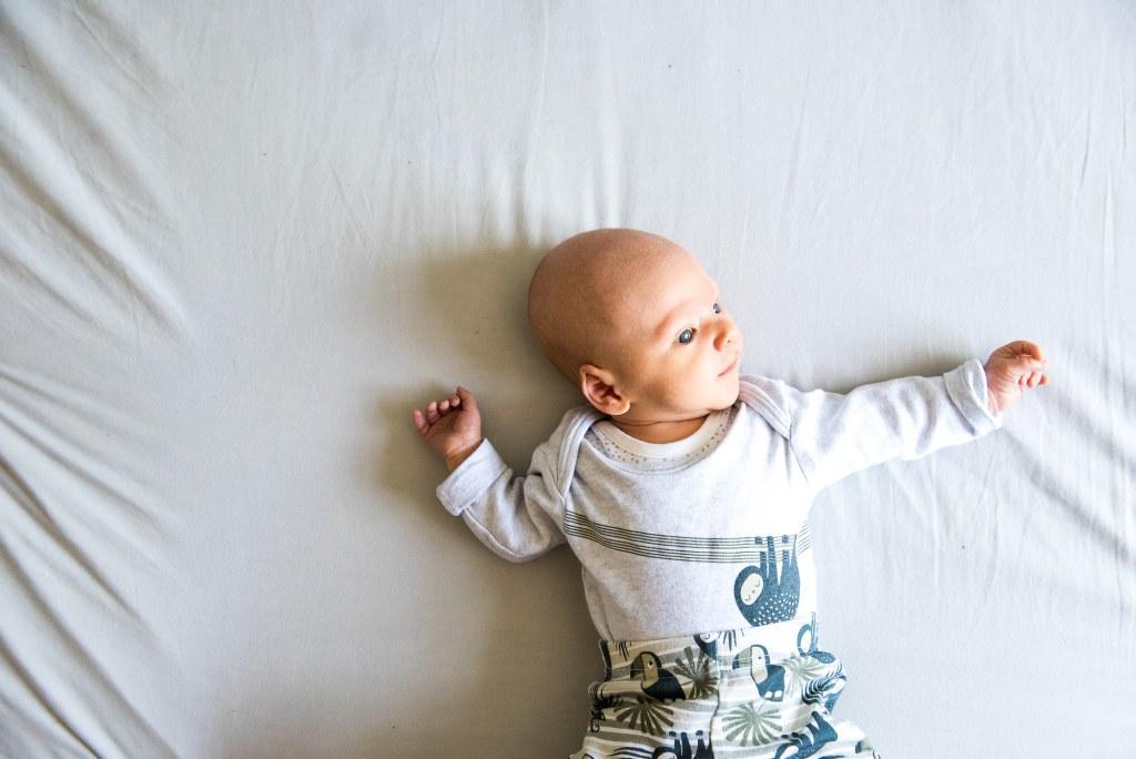 LGBT wedding photography, newborn baby lies on bed