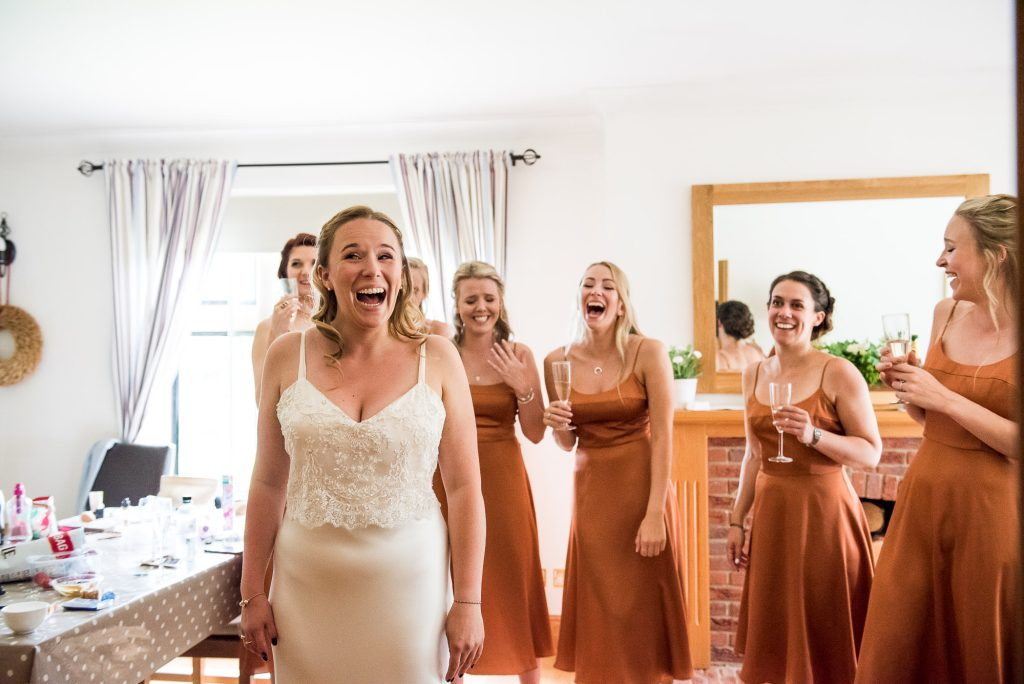 LGBT wedding photography, excited bride and bridesmaids laughing together