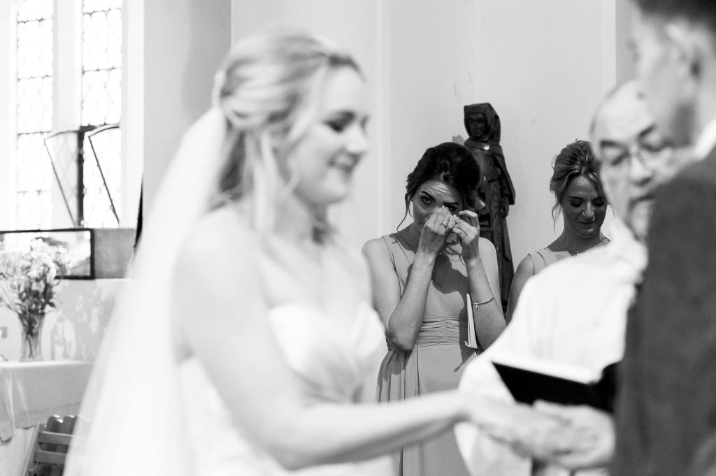 bridesmaid tears up as bride and groom say vows